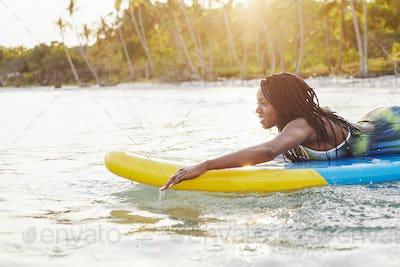 Woman swimming on sup board in sea
