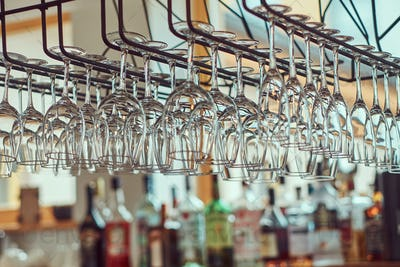 Close-up image of a wine glasses hanging in the bar above the bar counter.