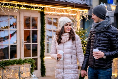 Romantic couple wearing warm clothes sitting on a bench in evening street