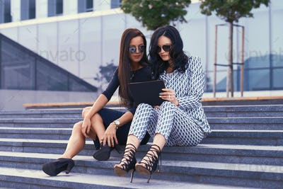 Two business women dressed in stylish formal clothes sitting on steps against a skyscraper.