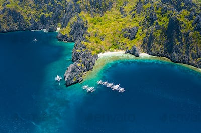 Aerial view of white boats in open sea close to tropical Miniloc Island. El Nido, Palawan island