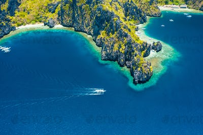 Aerial drone view of white boat in open sea, tropical island and beach of Miniloc Island. El Nido