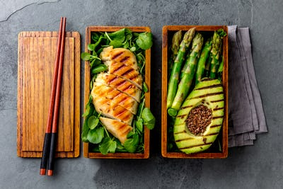 Healthy lunch in wooden japanese bento box. Balanced healthy food grilled chucken and avocado with