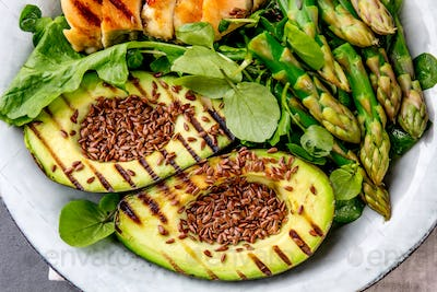 Healthy grilled chicken, grilled avocado and asparagus salad with linen seeds. Balanced lunch in