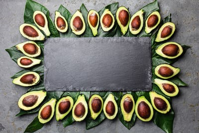 Avocado. Frame made from avocado palta and avocado tree leaves around slate board. Guacamole