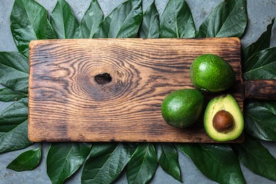 food background with fresh avocado, avocado tree leaves and wooden cutting board. Harvest concept