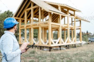 Builder with touchpad near the wooden house on the construction site
