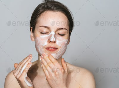 Young beautiful woman washing her face with hands by soap. Studio shot. Gray background.