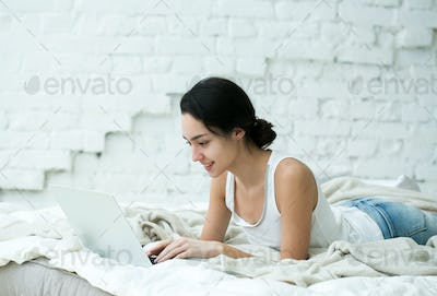 Beautiful Young Woman with Computer at home on sofa. Indoor shot.