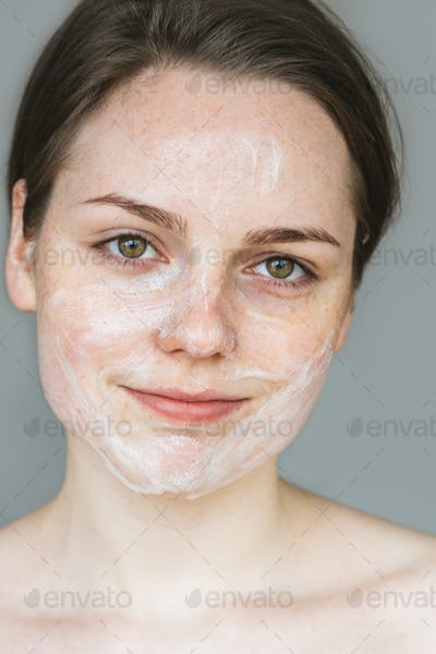 Young beautiful woman washing her face with hands by soap. Studio shot