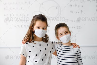 Girls with face mask back at school after covid-19 quarantine and lockdown