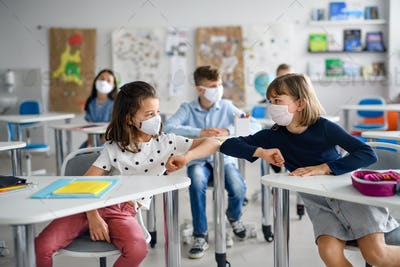 Children with face mask back at school after covid-19 quarantine and lockdown, greeting