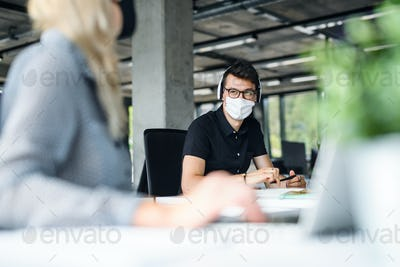 Young people with face masks back at work in office after lockdown, talking