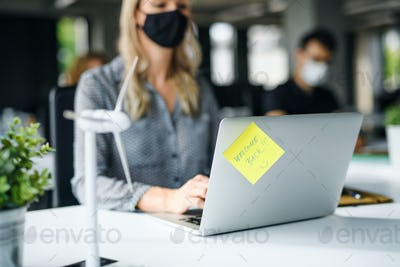 Unrecognizable young woman with face mask back at work in office after lockdown
