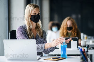 Young woman with face mask back at work in office after lockdown, disinfecting hands