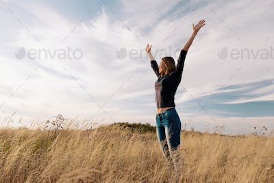 Young happy woman in a golden field on sunset.