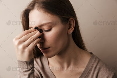 Photo of young beautiful woman with headache rubbing her forehead