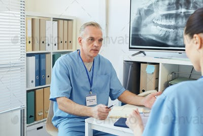 Mature Doctor Talking to Colleague in Clinic