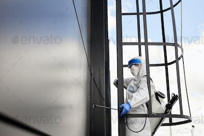 Worker Disinfecting Black Facade