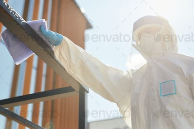 Worker Disinfecting rails Outdoors