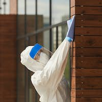 Female Worker Disinfecting Building