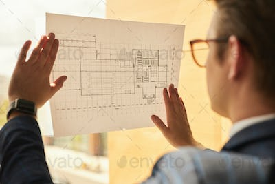 Real Estate Agent Looking at Plans