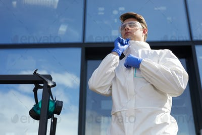 Young Worker Putting On Protective Suit Outdoors
