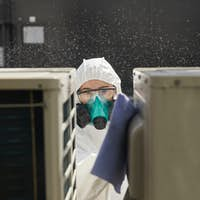 Female Worker Disinfecting Equipment Outdoors