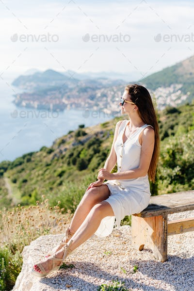 beautiful girl in summer dress relax with sea view and mountains
