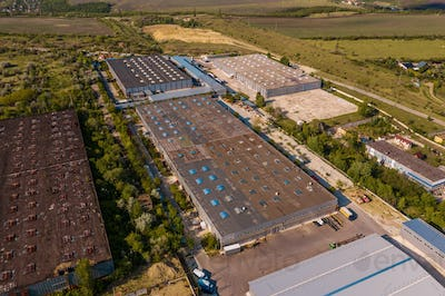 Top view industrial area warehouses in a green region