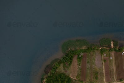 Top view of picturesque agricultural lands surrounded by water