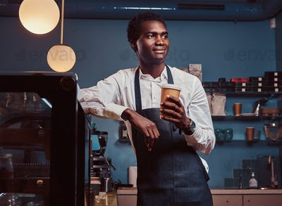 Handsome African barista at coffee shop.