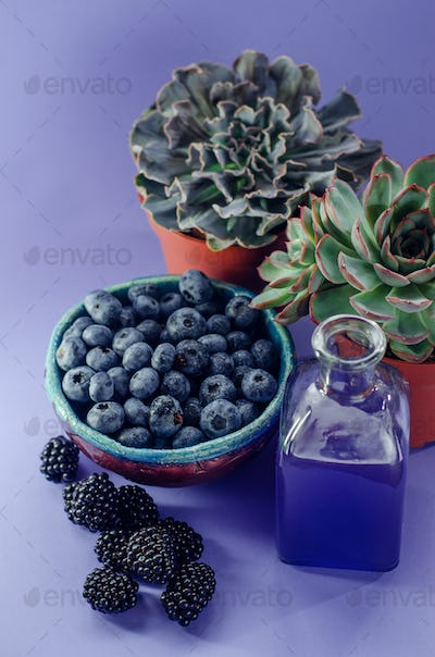 Blueberries in a plate and blackberries and raspberries on a blue background. Summer harvest.