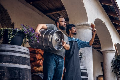 Two brewers in apron standing outdoors checking the quality of brewed drink at brewery factory.