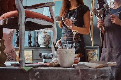 Female artist with her assistant in aprons painting vintage chair with paintbrush in workshop.