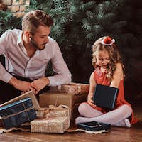 Dad and daughter sitting on a floor surrounded by gifts next to the Christmas tree at home.
