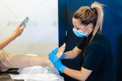 Beautician giving a pedicure painting her client's nails in a beauty centre