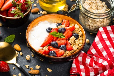 Greek yogurt granola with fresh berries on black stone table