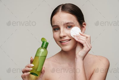 Image of pleased young shirtless woman using face lotion and smiling