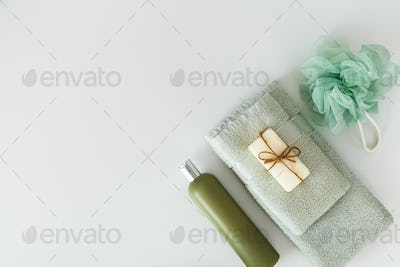 Bath towels with toiletries on white background. Flat lay, top view