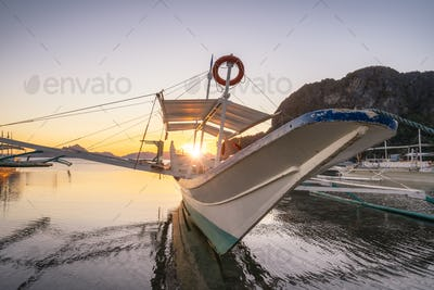 Trip boat on Corong corong beach, sunset flare shine. El Nido, Philippines
