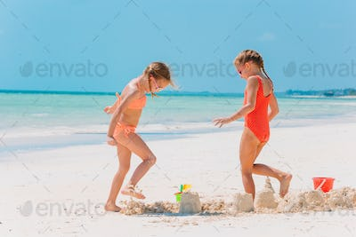Little happy funny girls have a lot of fun at tropical beach playing together