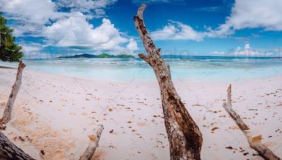 Impressive cloudscape above tropical island Praslin. Panorama of white sand paradise beach of anse
