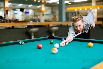 Handsome man aiming at ball