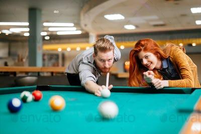 Couple playing billiards