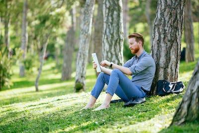 Businessman using tablet in park