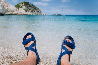 Young male feet wear blue flip-flop sandal sunbathing on pebble beach in front of blue sea water and