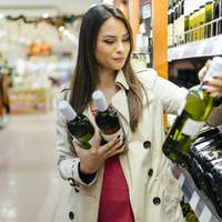 Woman deciding what wine to buy