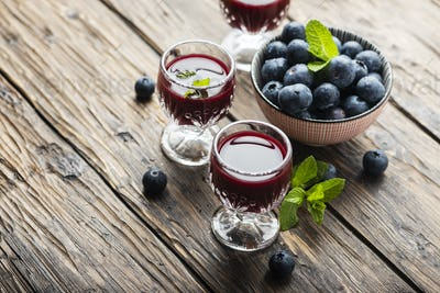 Sweet blueberry liqueur on the wooden table
