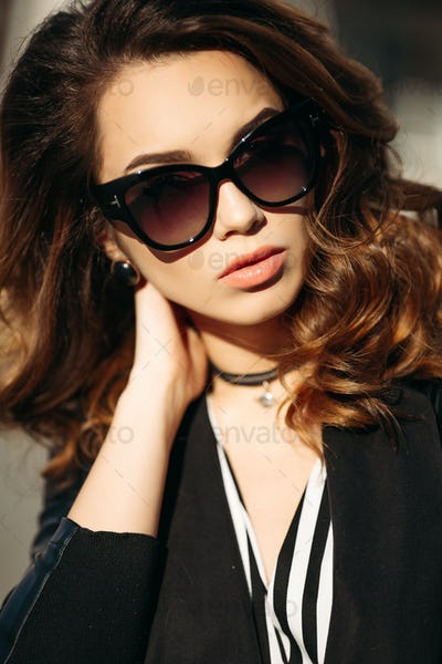 Sylish and beautiful brunette in sunglasses after beauty salon